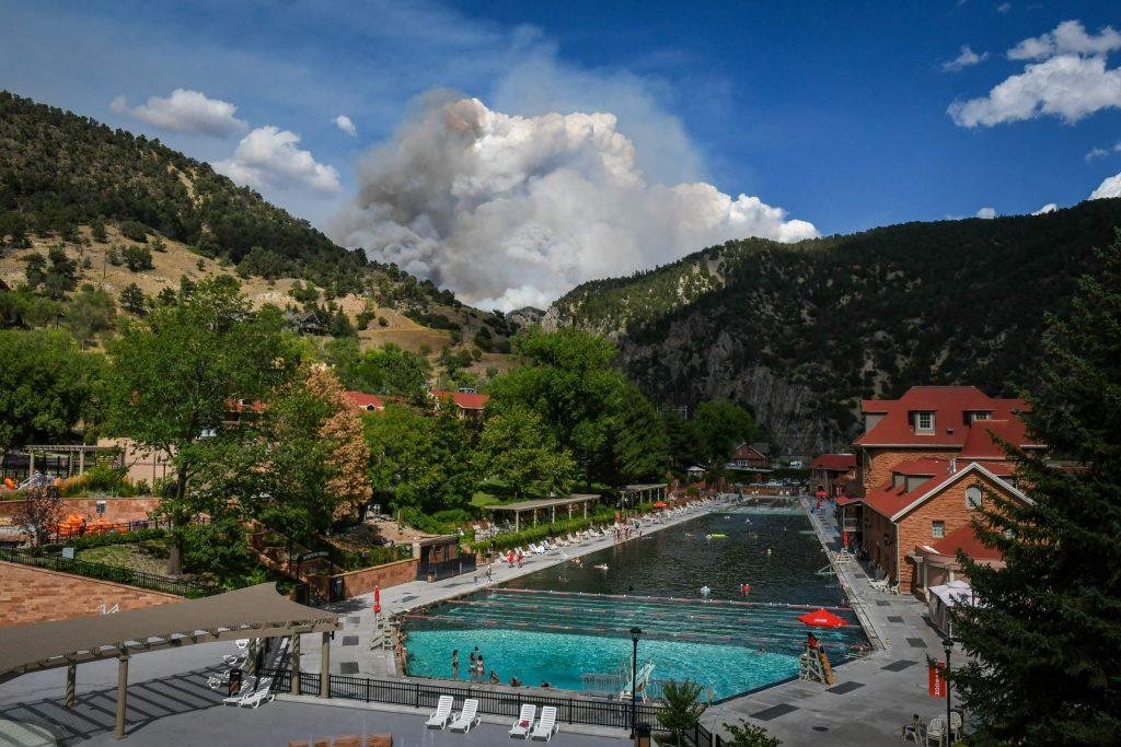 Smoke from the Grizzly Creek Fire billows behind the Glenwood Hot Springs Pool in Glenwood Canyon after the fire blew up again in No Name Creek on Wednesday afternoon.