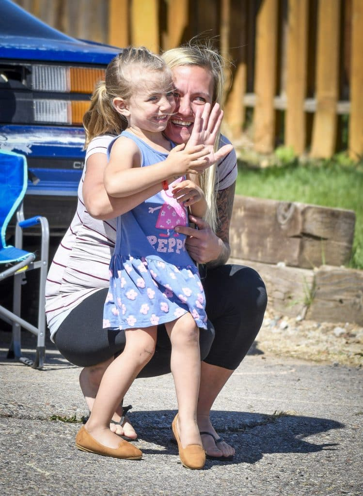 Alaya Shaffer and her mom Jessica wave as they brigade pulls in front of their home Saturday to wish her a happy birthday.