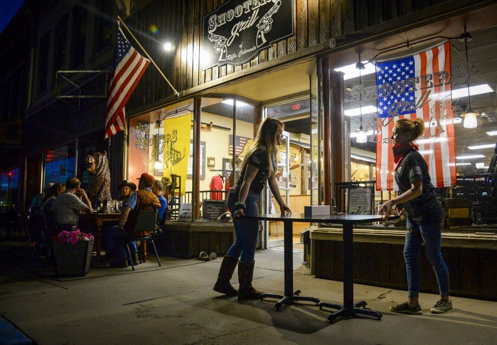 Employees at Shooters Grill carry tables inside as night time falls on Third Street in downtown Rifle last Thursday. After owner Lauren Boenert opened up for dine-in service and later serving customers outisde the western Garfield County buisness, the county health department suspended her license.