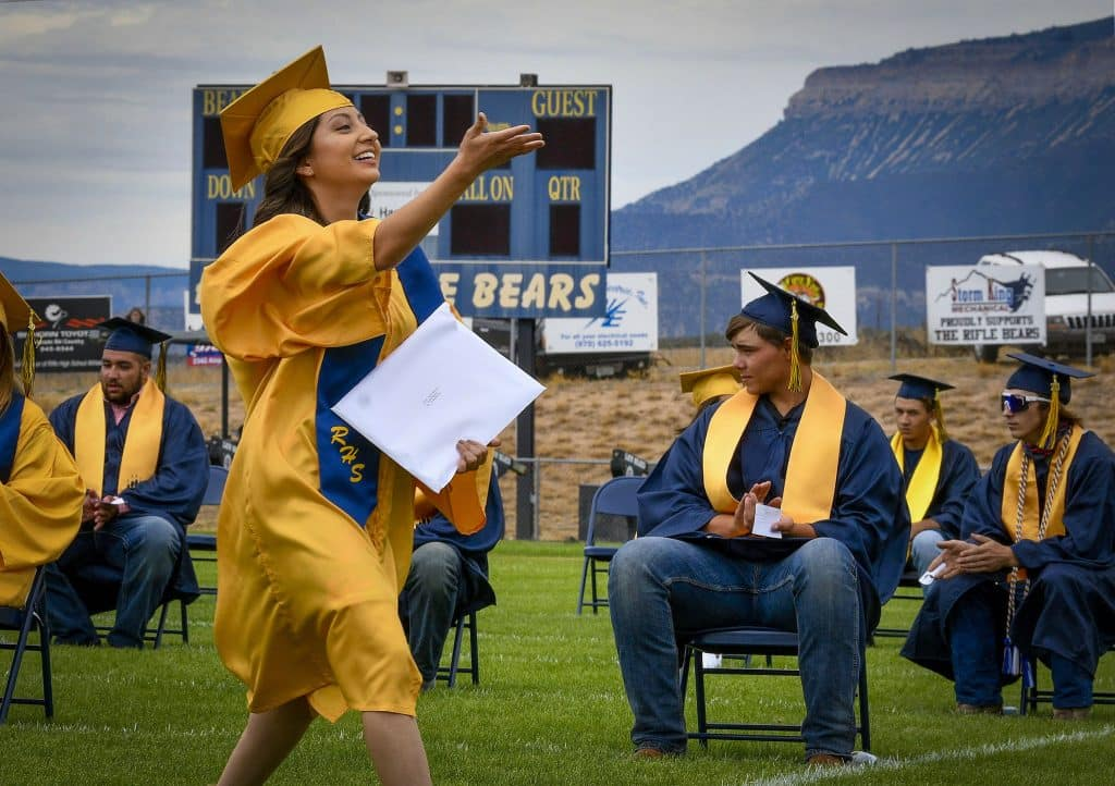 Yoselin Venzor Marquez blows a kiss to her family in the grandstand after recieveing her diploma Saturday at Bear Stadium in Rifle.