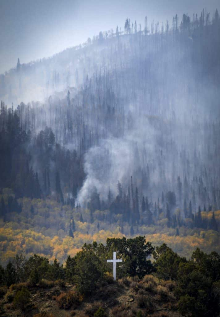 A lone white cross on a hilltop is flanked by the destruction of the Middle Mamm Fire South of Rifle. The fire which has been slowly burning erupted last weekend growing to over 900 acres.