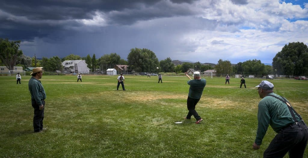Star BBC of Silt's Michael Hixson of SIlt belts the ball over the infield as a rain storm passes to the south of Silt during thrid-inning action.