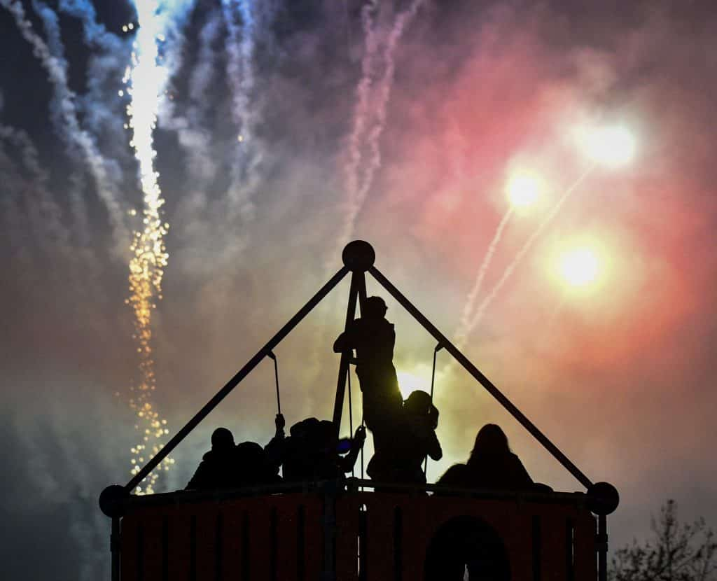 Children climb to the top the the jungle gym for a view of the show as fireworks light up the nightime sky above Centennial Park during Hometown Holday last Saturday in Rifle.