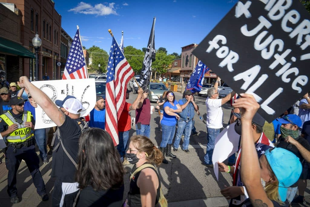 Black Lives Matter participants walk by pro-police supporters as they march through the intersection of Railroad Avenue and Third Street Friday evening in Rifle to mark the anniversary of Juneteenth. Hundreds of BLM supporters and pro-police supporter gathered in Rifle for the event.