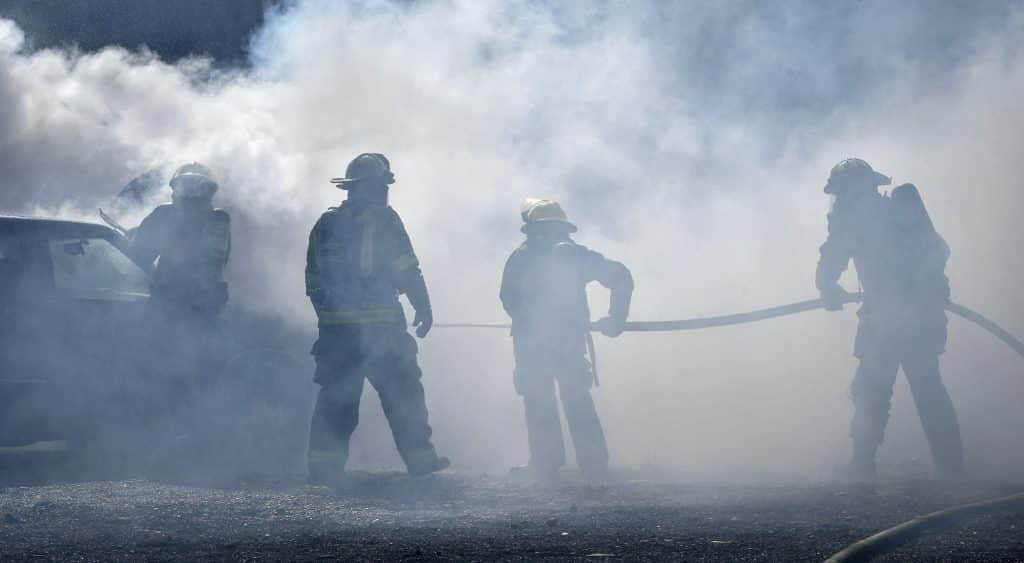 Under the watchfull eye of Terry Cox, division chief from Roaring Fork Fire Resuce (second from left) CMC Rifle Fire Academy cadets navigate a heavy cloud of smoke to extinguish a car fire during last Sunday's burn day in Glenwood Springs.