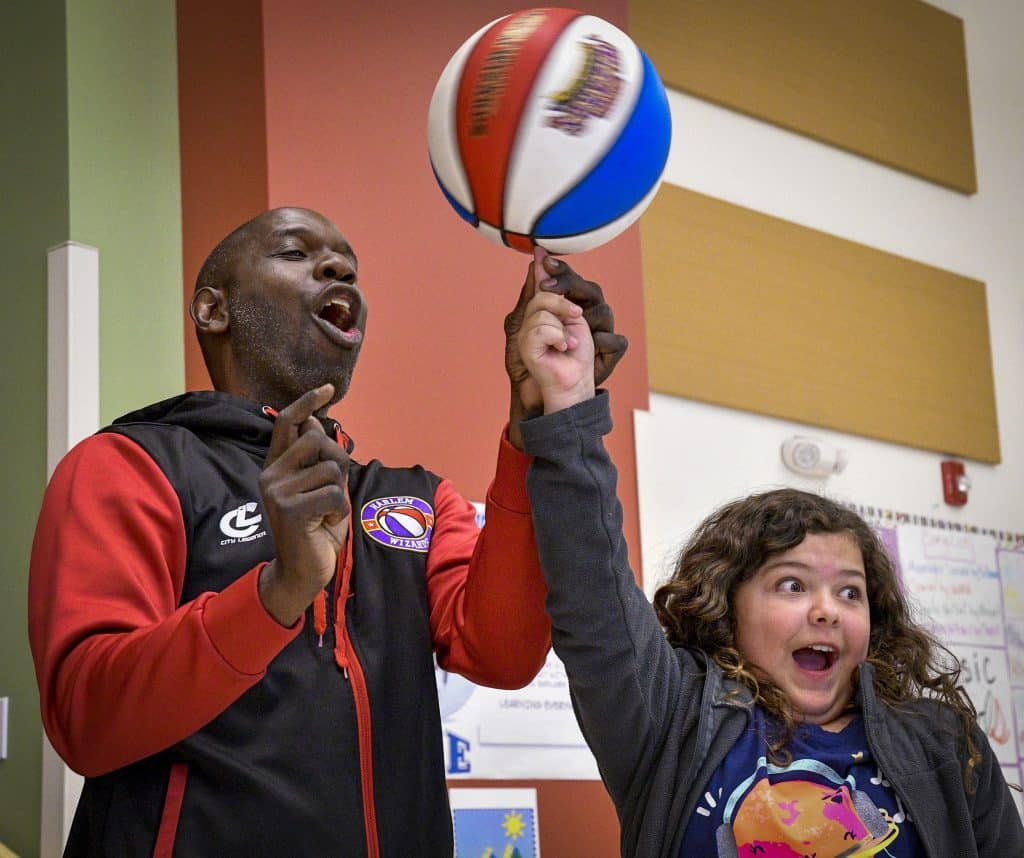 With a little help from Jones, Graham Mesa fifth grader Matilda Richardson spins a basketball on her fingers during Tuesday's school assembley during lunch.