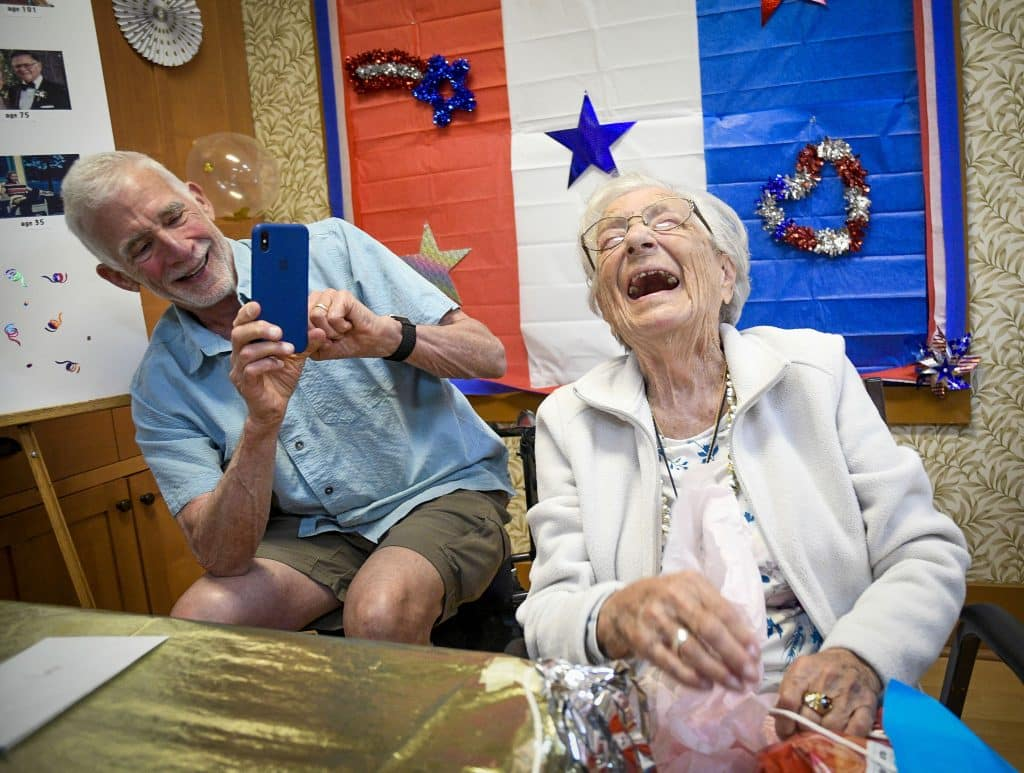 104-year-old Matty Baker bust out in laughter, as son-in-law Gerry Kaplin of Basalt videos her, after opening a gift from fellow resident of Chateau at Rifle during her birthday party last Saturday. The gift contained a party sized bag of Lays potato chips, Matty's favorite snack.