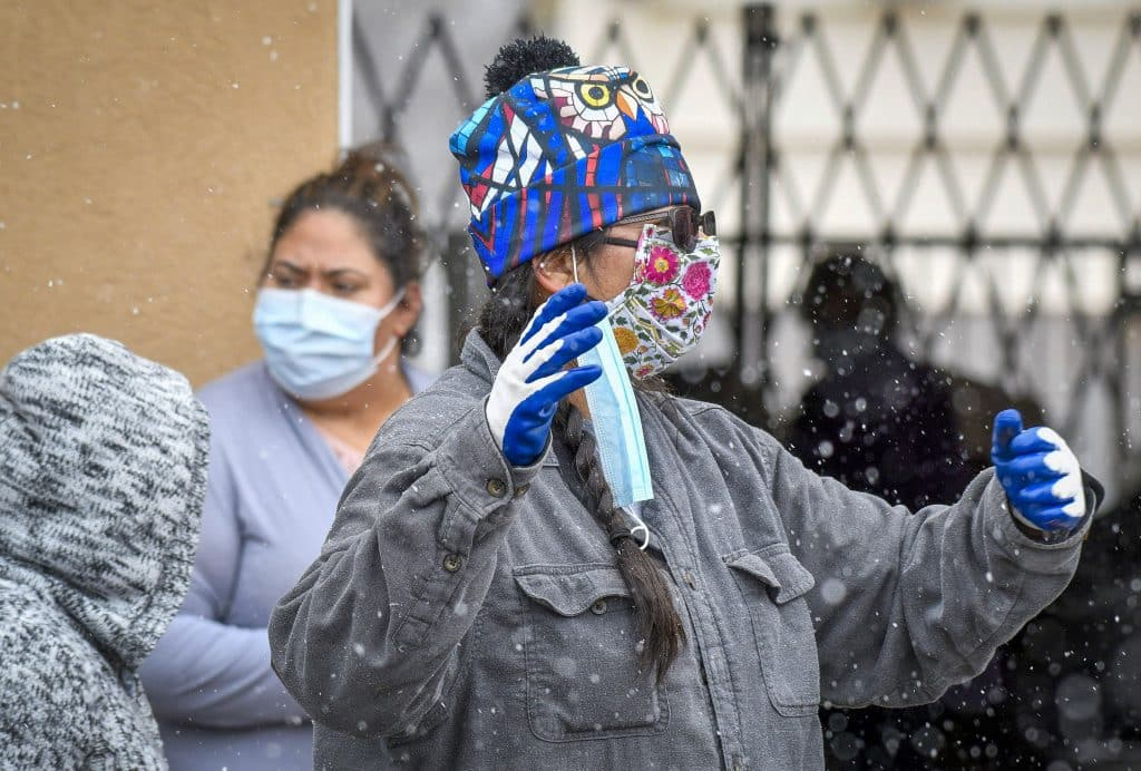 Snow falls as Monica Mull, with LIFT-UP directs traffic at Friday's food distribution in Rifle.