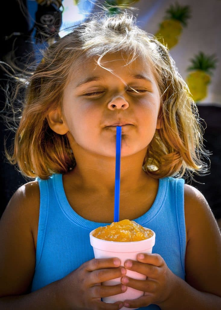 Kenzlee Bowler enjoys the cool relief of a sno cone Friday at Rifle Police Department. Robin Steffen, public information officer for the department said she wanted to seize the opportunity to reconnect with the community with the event.  More than 400 sno cones were given out last Friday.