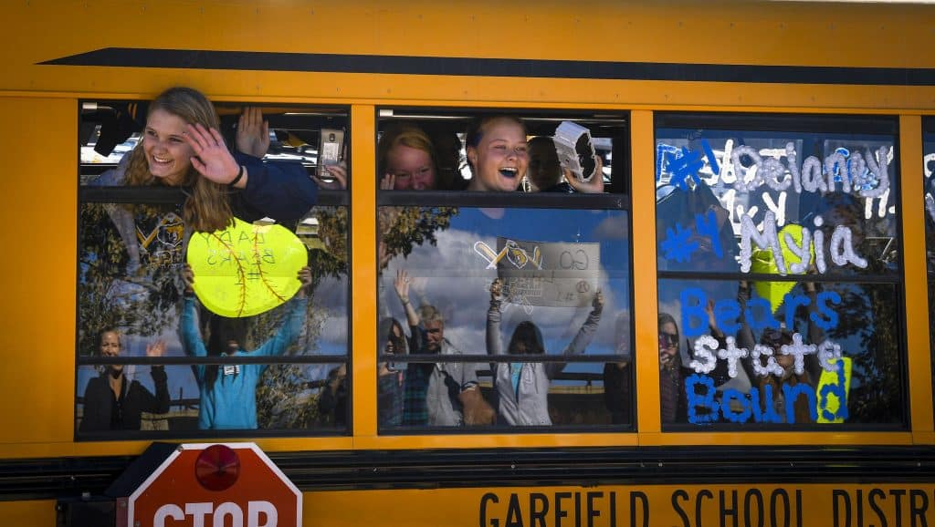 The Rifle Bears softball team react to the crowd gathered at the roundabouts near I-70 to send them off as they trave to Aurora for the state softball torunament. More than 40 family members, friends and fans gathered Thursday for the send off as the team was excorted out of town by the Rifle Police Department.