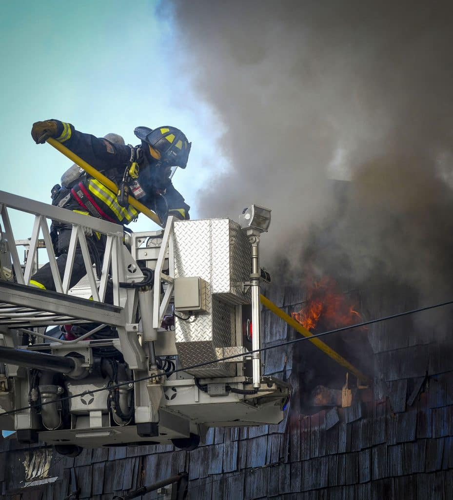A firefighter punches a vent into the attic of the Carquest Auto Parts building during last week structure fire in Rifle.