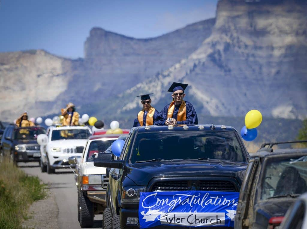 Flanked by Anvil Points and the Roan Plateau Rifle High School Class of 2020 begins their processional down W Sixteenth Streetas they loop through town last Saturday.