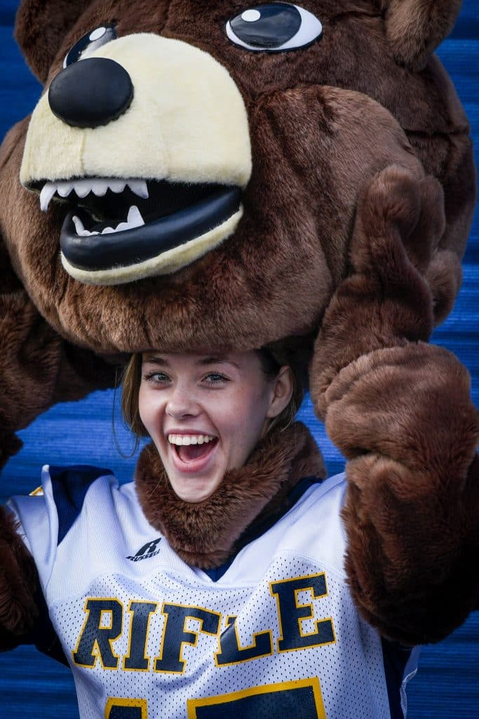 The Rifle High School mascot is all smiles as the cheer team prepares for the game against Grand Valley.