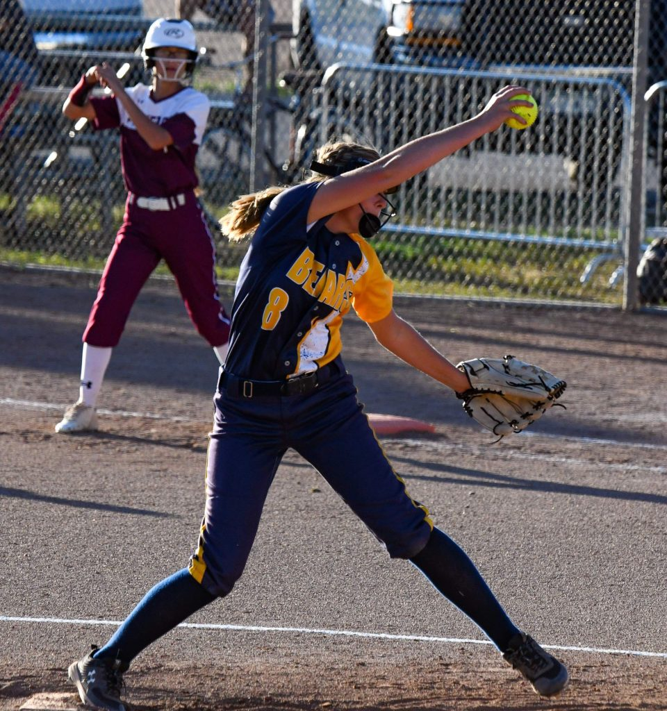 Rifle Bear Blayke Hostettler winds up to throw the pitch while the runner on first prepares to leave the base during Tuesday night's home game against Palisade.
